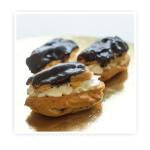 Ciasteczka bankietowe, mini eklerki z naturalną bitą śmietaną Delikatna masa kremowa na biszkoptowym spodzie. Całość wykończona czekoladową polewą.