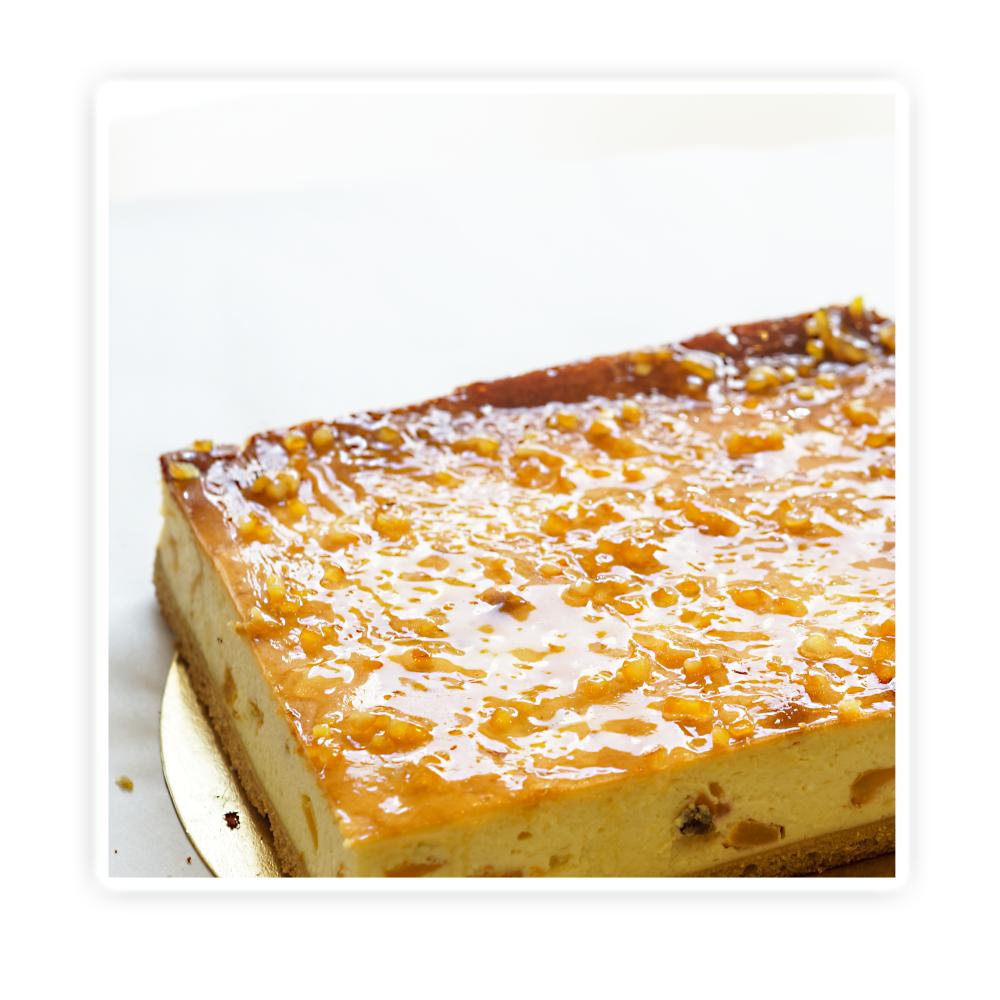 Sernik z brzoskwinią - Puszysta masa serowa z dodatkiem brzoskwiń na biszoptowo-tłuszczowy spodzie , całość po żelowana i posypana skórką pomaranczową.