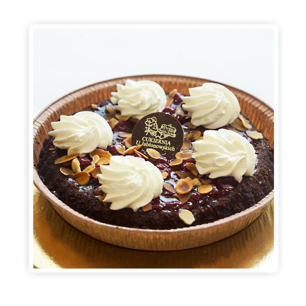 Anielska Pokusa - Biszkopt mocno czekoladowy nasączony , wypełniony czekoladową bitą śmietaną , frużeliną wiśniową. Wykończona płatkami migdałowymi i delikatną bitą śmietaną.